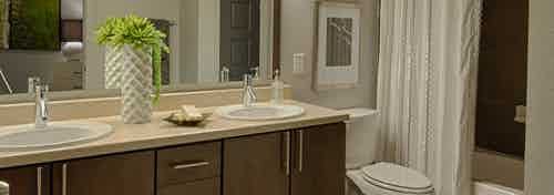AMLI Uptown apartment bathroom with double vanity, large mirror, dark wood cabinets with designer hardware and garden tub