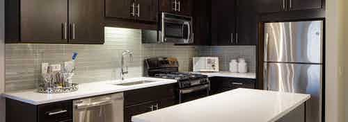 AMLI Lofts kitchen with a quartz island alongside dark wooden cabinets and a taupe backsplash with stainless steel appliances