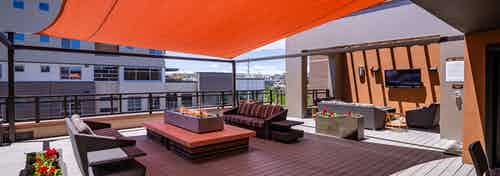 The rooftop at AMLI Riverfront Park apartments featuring a television and couches and a fire pit and an orange overhead shade