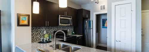 A kitchen at AMLI Arista apartments with a sink and fridge and overhead lighting as well as the front door in the background
