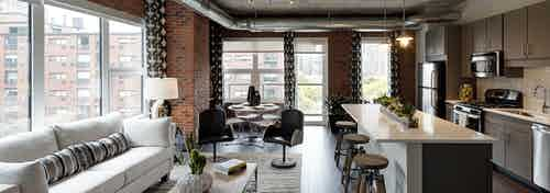 Interior view of living room and kitchen at AMLI Lofts featuring exposed brick wall with dark flooring and quartz countertops
