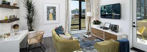 Interior of AMLI Marina Del Rey model living room with couch, coffee table and desk in front of large window facing marina