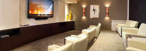 """Interior view of private screening room with 80"""" HDTV and beige leather club seating at AMLI River Oaks apartment building"""