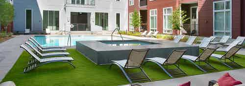 Exterior view of the pool area at AMLI Denargo Market with a hot tub and lounge chairs on turf with apartment in background