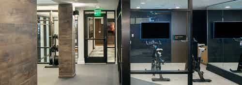 Spin cycles and fitness on demand featured at AMLI Riverfront Green apartments with a view into the elevator hallway
