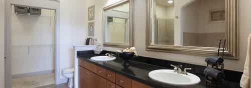 Interior view of AMLI Las Colinas apartment bathroom with black granite double vanity, wood cabinets and walk-in closet