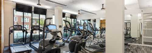 AMLI Frisco Crossing fitness center with treadmills and other cardio machines and mounted TVs and ceiling fans above