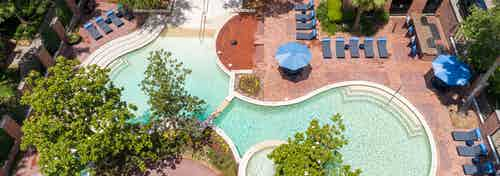 Daytime aerial view of curvy swimming pool with lounge chairs and umbrellas at AMLI Memorial Heights apartment building