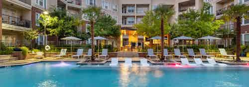 Nighttime view of AMLI Frisco Crossing apartments swimming pool area with lounge seating, umbrellas and palm trees