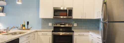 A kitchen of an apartment at AMLI Sawgrass Village with a stainless steel microwave nested in white cabinets above an oven