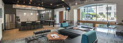 Interior view of resident lounge at AMLI Las Colinas apartment building with resident kitchen and game tables and seating