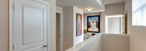 Upstairs townhome hallway at AMLI Memorial Heights apartments with window and two pieces of colorful artwork on walls