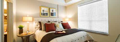 AMLI River Oaks apartment bedroom with bed with upholstered headboard, two nightstands with lamps and window with blinds