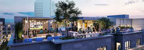 Nighttime rendering of AMLI Old Pasadena rooftop deck lounge lined with plants and lights with city buildings in background