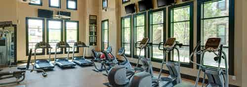 Interior of fitness center at AMLI at Escena apartments with treadmills and cardio machines and TVs and two-story windows