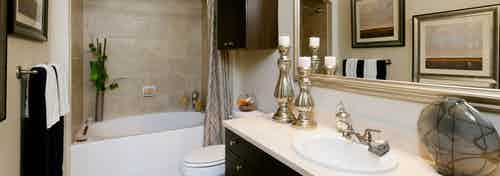 AMLI River Oaks apartment bathroom with granite vanity, large mirror, dark wood cabinets and garden tub with tile surround
