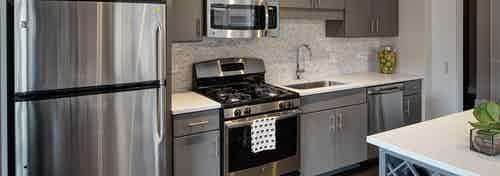 An AMLI Lofts kitchen containing stainless steel appliances and grey cabinets paired with quartz countertops and a backsplash