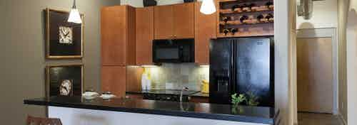 Interior view of AMLI Las Colinas apartment kitchen with black appliances, granite countertops and tile backsplash