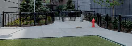 Exterior view of the gated dog run with artificial turf at the AMLI Lofts apartment community in the bright day time