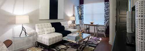 Interior view of beautifully decorated living room with wood floors and large window at AMLI Uptown apartment building