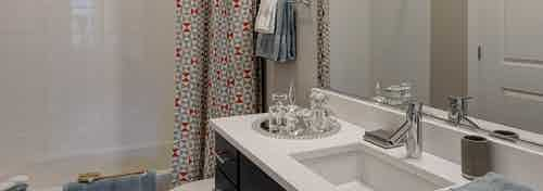 Interior view of a bathroom at AMLI Lofts with dark cabinets and a white countertop and bathtub with a patterned red curtain