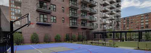 Exterior view of the sport court and multi-purpose green space at AMLI Lofts apartment community including a basketball hoop