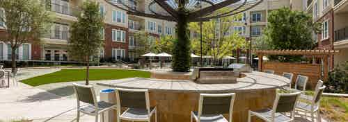 Daytime view of courtyard grill station at AMLI Frisco Crossing apartments with seating and pool area in background