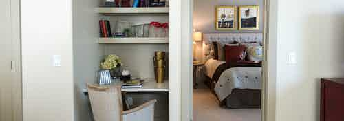 Interior view of built-in desk and shelves and a glimpse into beautifully decorated bedroom at AMLI River Oaks apartments