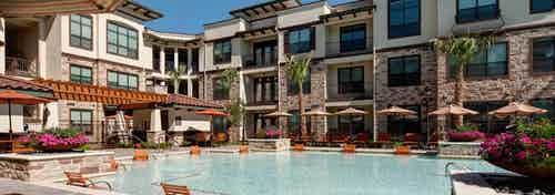 Daytime view of AMLI at Escena apartment building swimming pool with lounge seating in and out of water and umbrellas