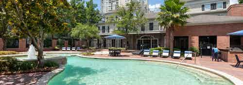 Daytime exterior view of AMLI Memorial Heights swimming pool with lounge seating, umbrellas, grill station and trees