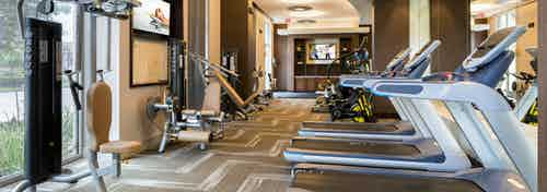 Fully equipped fitness center at AMLI River Oaks apartment building with strength machines at left and tread mills at right