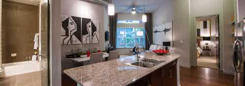 Interior view of AMLI Uptown apartment from granite island with glimpse into bathroom and dining and living areas and bedroom