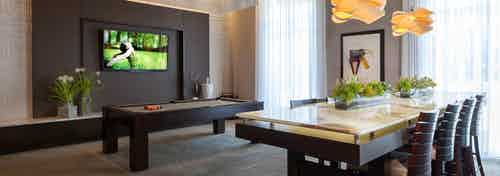 AMLI River Oaks resident lounge with billiards table, big screen TV on dark brown wall and long table with eight chairs