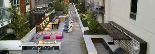 Aerial dusk view of gaming courtyard at AMLI Park Broadway with plentiful seating and grilling station and fire pit