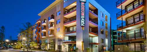 Nighttime exterior view of AMLI Ponce Park apartment community brick facade with sign above building entrance and trees