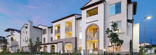 Exterior dusk rendering of AMLI Spanish HIlls apartment building with lit patios and arched entry ways surrounded by greenery