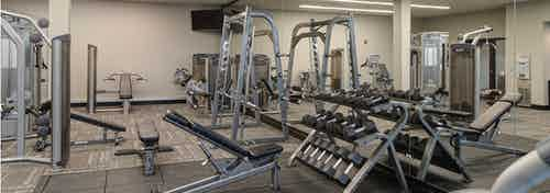 Expansive fitness center at AMLI Deerfield apartment community with various weight machines as well as free weights