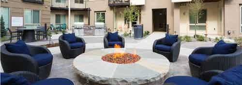Exterior view of a fire pit area at AMLI Cherry Creek apartments with many plush blue chairs and table with chairs and trees