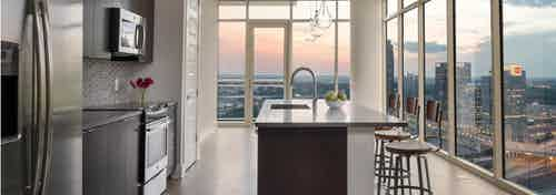 Kitchen at AMLI Arts Center with floor to ceiling windows showing a sunset city view with an island and industrial barstools