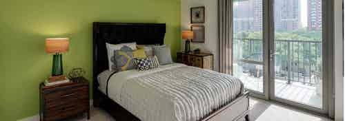 An AMLI 900 apartment bedroom with vibrant decor accents and large glass doors leading to a balcony with city views