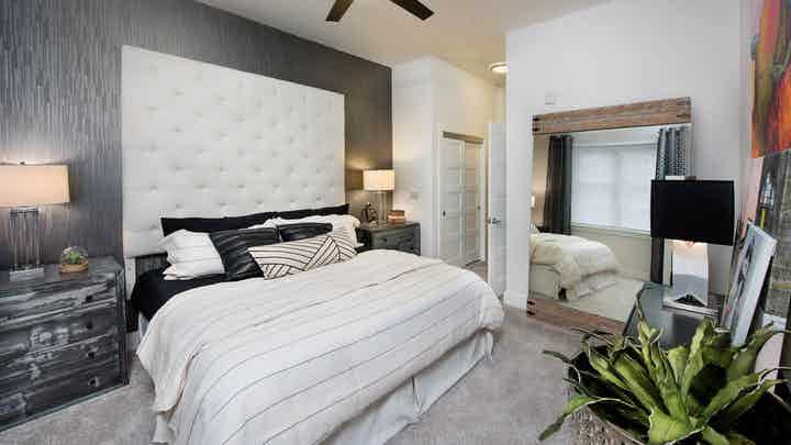 AMLI Buckhead bedroom with carpet and light walls with a tall ivory headboard and matching bedding with black throw pillows