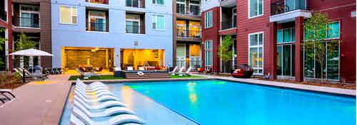 A pool at AMLI Denargo Market apartments with lounge chairs and umbrellas and stairs up to a hot tub with view of balconies