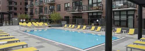 Exterior view of the swimming pool at AMLI Lofts apartment community facing the building facade in the daytime light