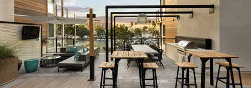 Daytime view of lounge deck overlooking Mother's Beach with tables, grill station and big screen TV at AMLI Marina Del Rey