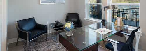 Interior of office at AMLI South Shore with a scenic window view and a large glass desk across from two leather chairs