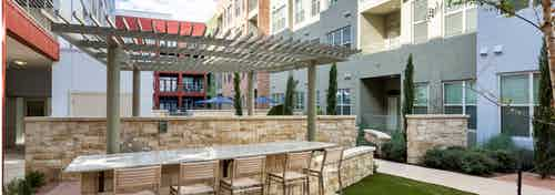 Outdoor barbecue area at AMLI at Mueller with bar seating in front of a pergola with view of exterior building facade