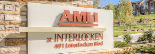 A street facing sign at AMLI Interlocken apartments made of stone with the property address and trees and bushes and driveway