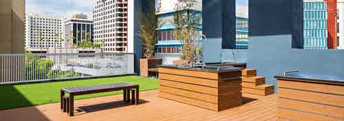 Daytime view of Rooftop pet park with dog spa overlooking the city at AMLI Lex on Orange apartments with turf rug and bench
