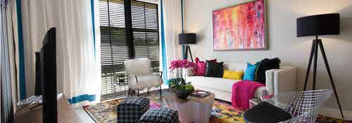 Interior of an AMLI Dadeland apartment living area with white sofa, pillows, modern colorful artwork and black floor lamps