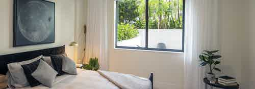 AMLI Midtown Miami apartment bedroom with window overlooking patio and bed and small table with plant and books